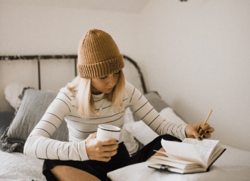 settle in at home - woman sitting on bed with coffee and notebook