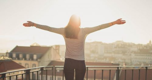 woman stretching out her arms to the sun on a balcony