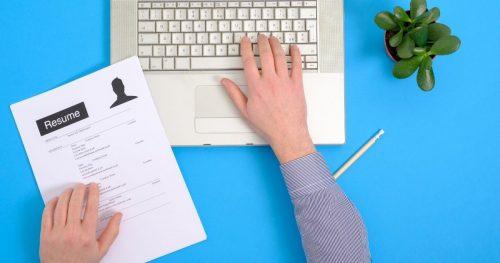 man holding resume typing on laptop