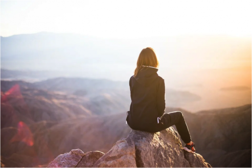 woman sitting on a mountain top