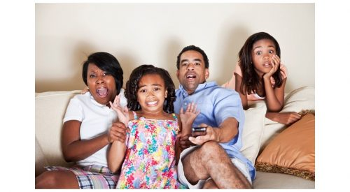 Mixed race family reacting in surprise to the tv