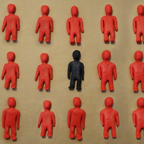 Deaf Identity - one black figurine amongst all red