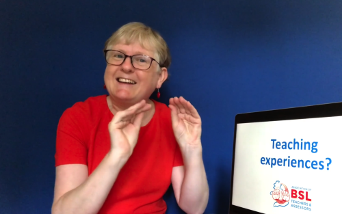 Emma demonstrating a sign next to a monitor